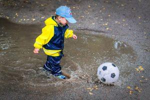 子供がボールを蹴っている画像