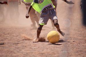 砂の上でサッカーをする子供
